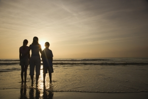 Silhouette of three family members at beach